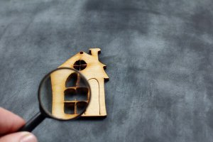 What type of insurance do home inspectors need? House under magnifier.